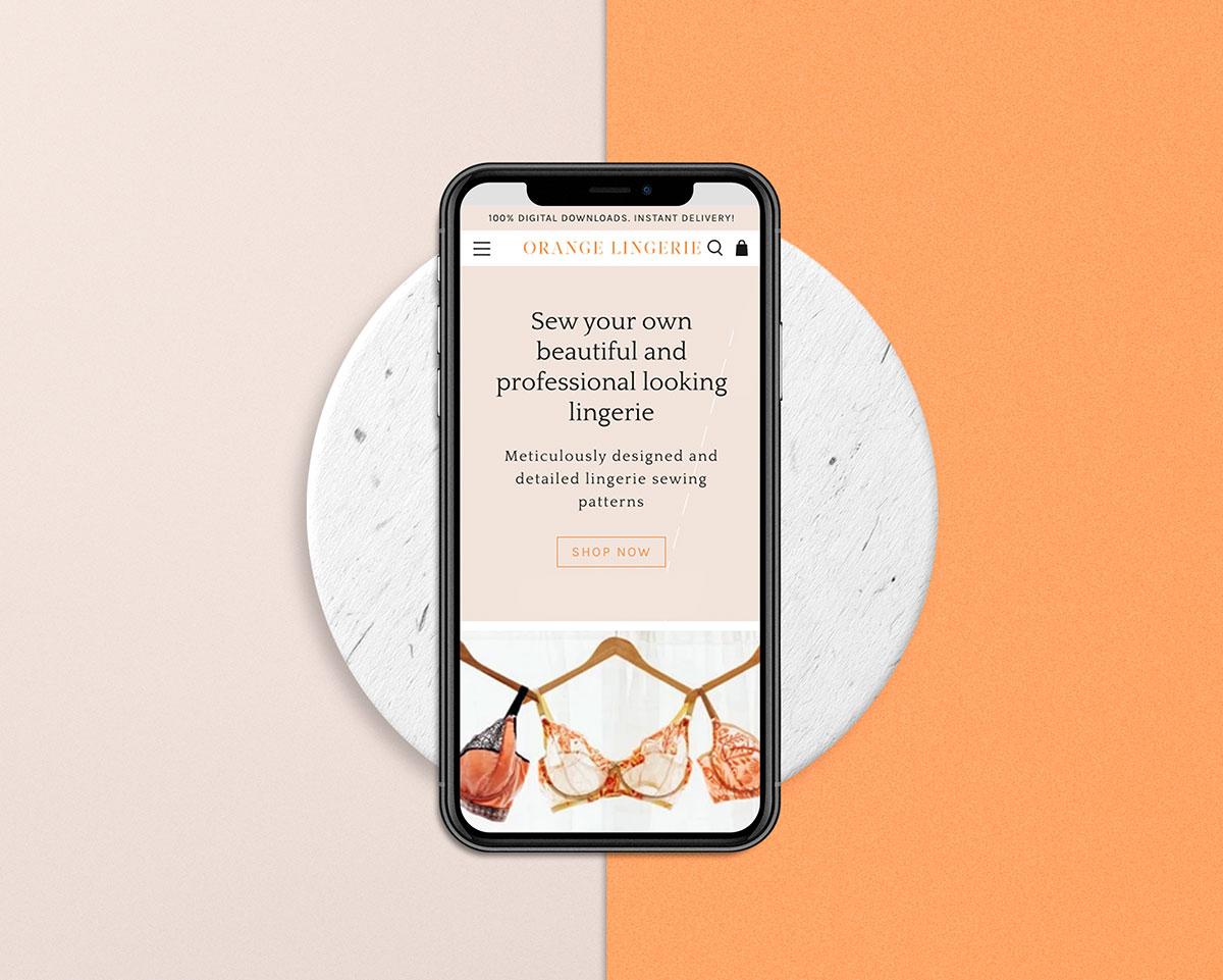 orange lingerie homepage design on an iphone with a circle background