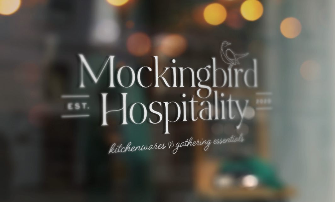store window mockup of the primary logo of Mockingbird Hospitality